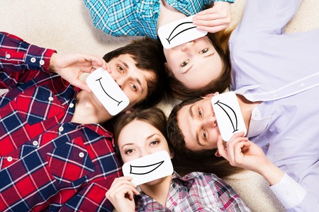 four young men lie together, applied to the face card with smiles photo