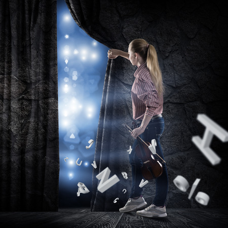 image of a young woman pushes the curtain behind which concert lights photo