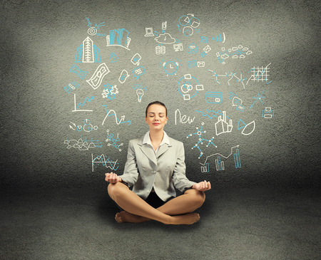 business woman meditating on floor, wall charts and diagrams are drawn photo