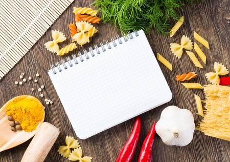 food menu: spices, pasta and vegetables around notebook on a wooden table
