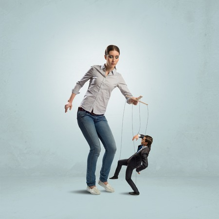puppeteer controls a businessman holding his strings, the concept of control of business photo