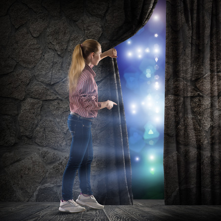image of a young woman, changes reality, looking at the lights of a stone wall