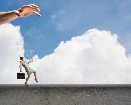 manipulate: business woman puppet walks on the concrete parapet