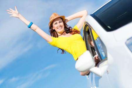 young woman got out of the car window, holds the hand hat, waving his hand and laughing photo