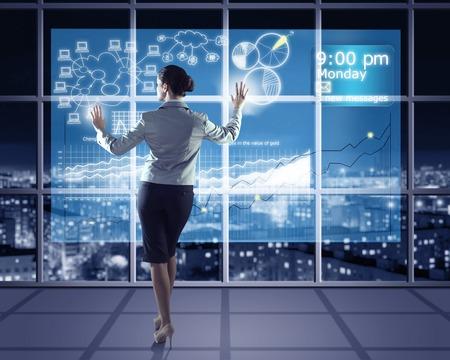 Geschäftsfrau, die mit modernen virtuellen Technologien steht zurück, Hände Berühren des Bildschirms Standard-Bild - 28018902