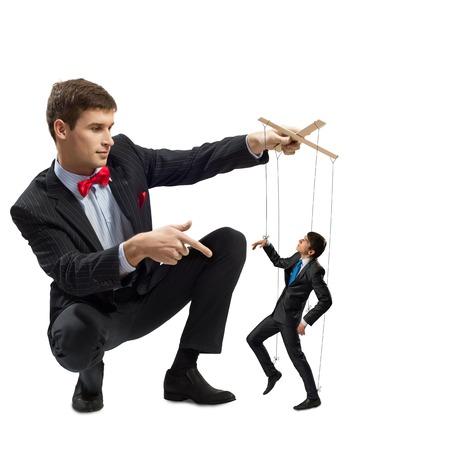 obedecer: titiritero tiene el hombre de negocios de marionetas en la cuerda floja Foto de archivo