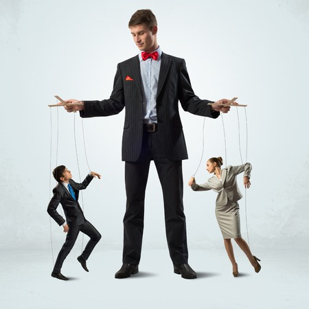 manipulate: puppeteer keeps business people puppets, concept control business