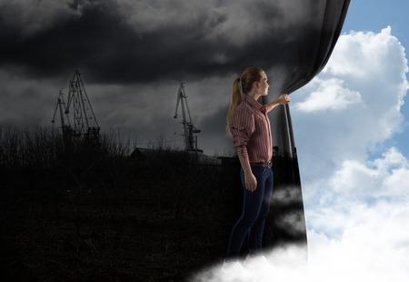 若い女性のイメージの雲を見てカーテンをプッシュします。