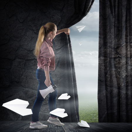 image of a young woman pushes the curtain looking at flying paper airplanes photo