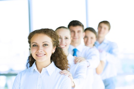 portrait of a young business woman standing in line with colleagues, concept of teamwork