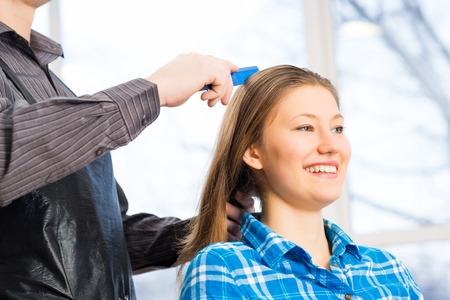 male hairdresser puts woman s hair in a hairdressing salon photo