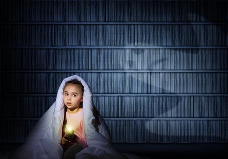 Beeld van een meisje onder de dekens met een zaklamp in de nacht bang voor spoken Stockfoto - 28632276
