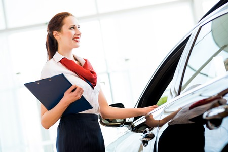 car dealer: portrait of a young woman in a showroom consultant