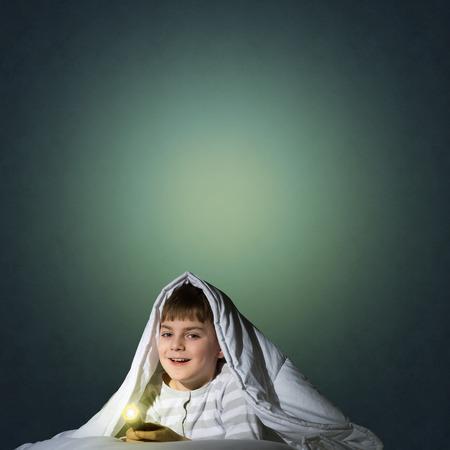 niño abrigado: imagen de un niño debajo de las sábanas con una linterna