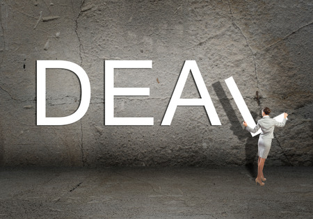 adds: young businesswoman adds deal word on concrete wall