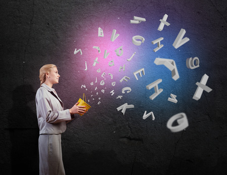 narrative: Young woman holding bucket with letters flying out Stock Photo