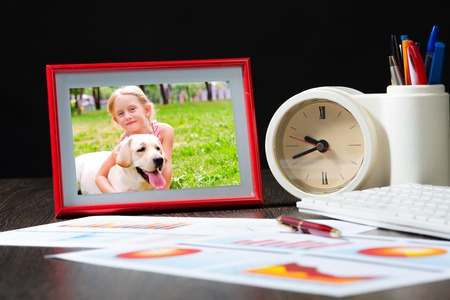 photo frame, business paper with growth graph, table clocks and keyboard  Workplace of the businessman  photo
