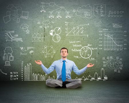 바닥에 명상 비즈니스 사람 (남자)의 이미지는 벽 차트 및 다이어그램을 그려