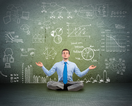 image of a business man meditating on floor, wall charts and diagrams are drawn Фото со стока