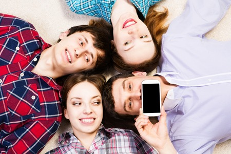 four young people are together, the young man pressed his lips to the phone photo