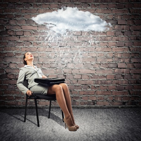 image of a young business woman looking at the cloud with lightning photo