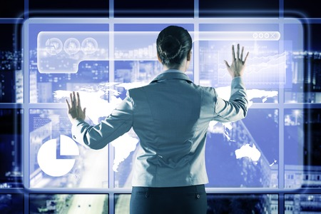 businesswoman working with modern virtual technologies, stands back, hands touching the screen