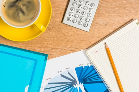 image of a cup of coffee, calculator, notepad and pencil  business still life photo