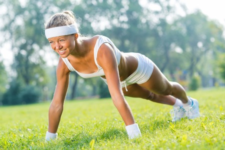 Young woman in sport wear doing push ups in park