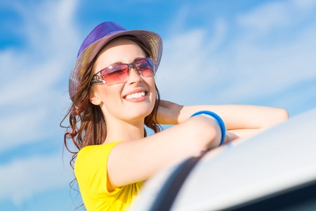 young woman got out of the car window, holds the hand hat and laughing photo