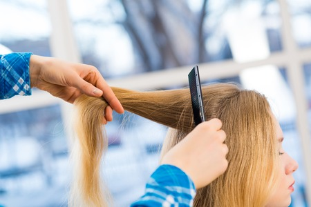 close up combing hair at the hairdresser photo