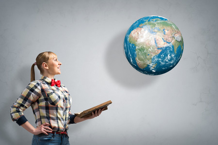 Young woman in casual with book in hands  Elements of this image are furnished by NASA photo