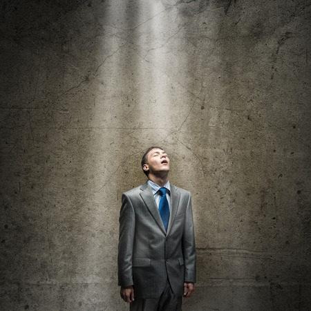 unskilled: Young tired businessman standing with closed eyes