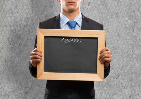 Young businessman holding chalkboard with word agenda photo