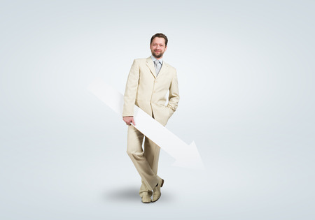 decreasing: Handsome businessman with white blank arrow  Place for text Stock Photo
