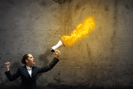 agitation: Young upset businesswoman screaming furiously in megaphone