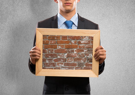Close up of businessman holding frame with brick texture photo