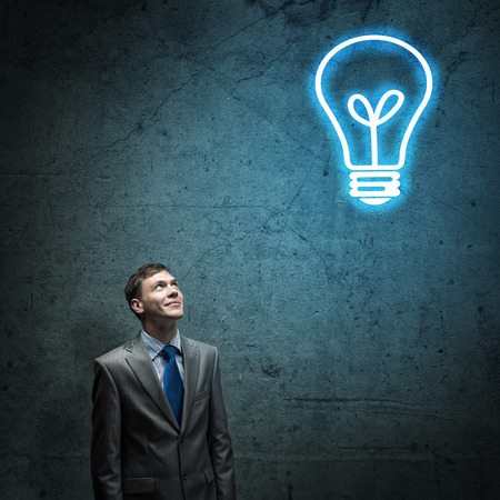 Young thoughtful businessman looking above at light bulb Stock Photo