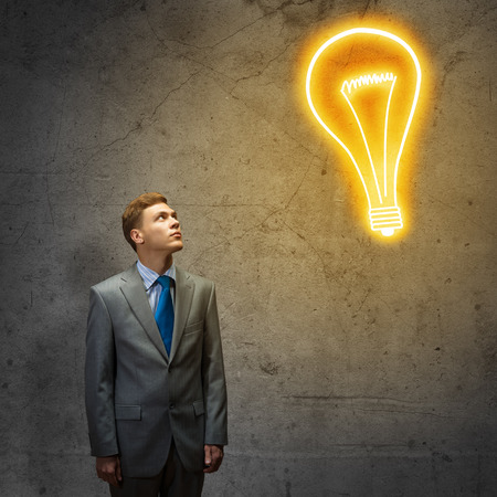 power of the mind: Young thoughtful businessman looking above at light bulb Stock Photo