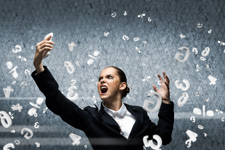 Young aggressive businesswoman screaming in mobile phone photo