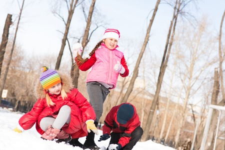 actively: Children in Winter Park playing snowballs, actively spending time outdoors Stock Photo