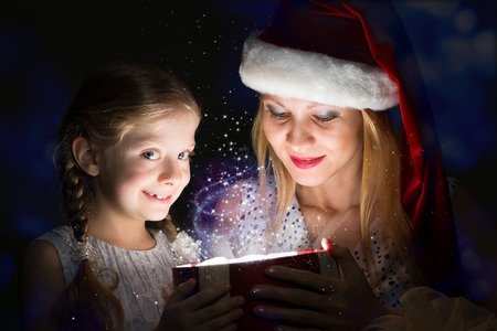mother in Santa Claus cap and daughter opened a box with Christmas gift boxes of shining light and magic photo