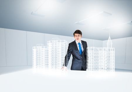Young businessman and digital model of construction project photo