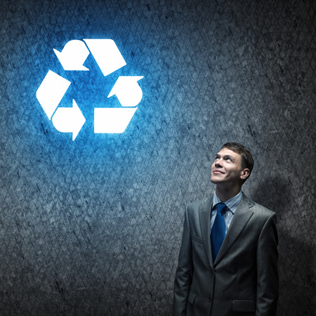 Young businessman looking at recycle symbol above head photo