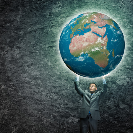 Young businessman holding Earth planet high above head          photo