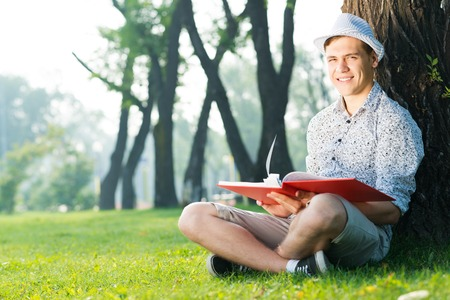 young man wearing a hat reading a book in the park photo