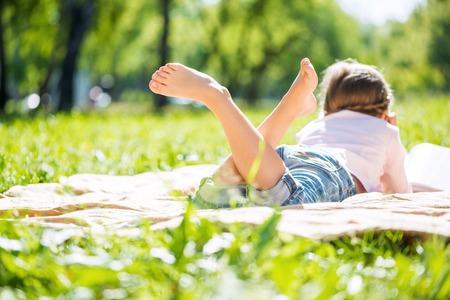 여름 공원에 누워있는 어린 소녀의 후면보기