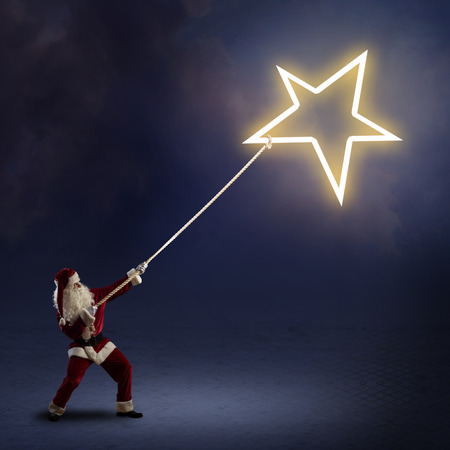 newyear night: Santa Claus pulls the shining star using a rope