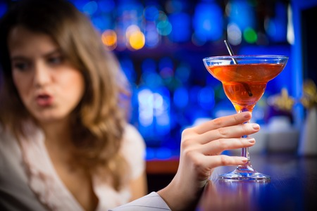 close-up of hands holding the leg of a martini glass with red alcoholic beverage in the background girl photo