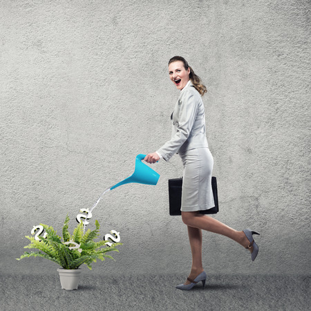 Businesswoman with can watering dollar money tree photo