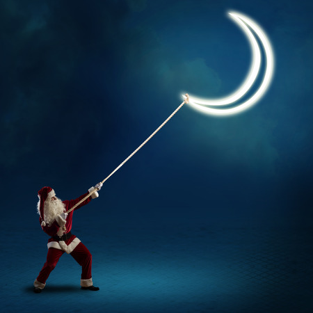 Santa Claus pulls the moon using a rope photo